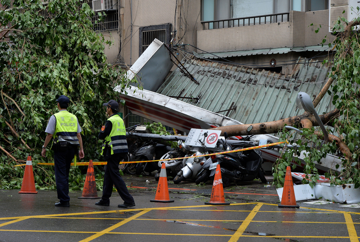 Police walk past vehicles and a store damaged by fallen trees after Typhoon Soulik hit Taipei on July 13, 2013. (MARK RALSTON
