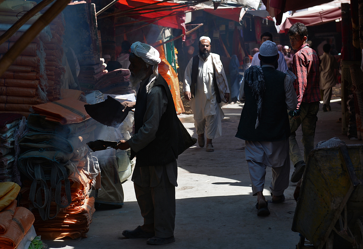 An Afghan trader fans herbs called spand, believed to ward off misfortune and evil spirits when burned, at a market in Kabul
