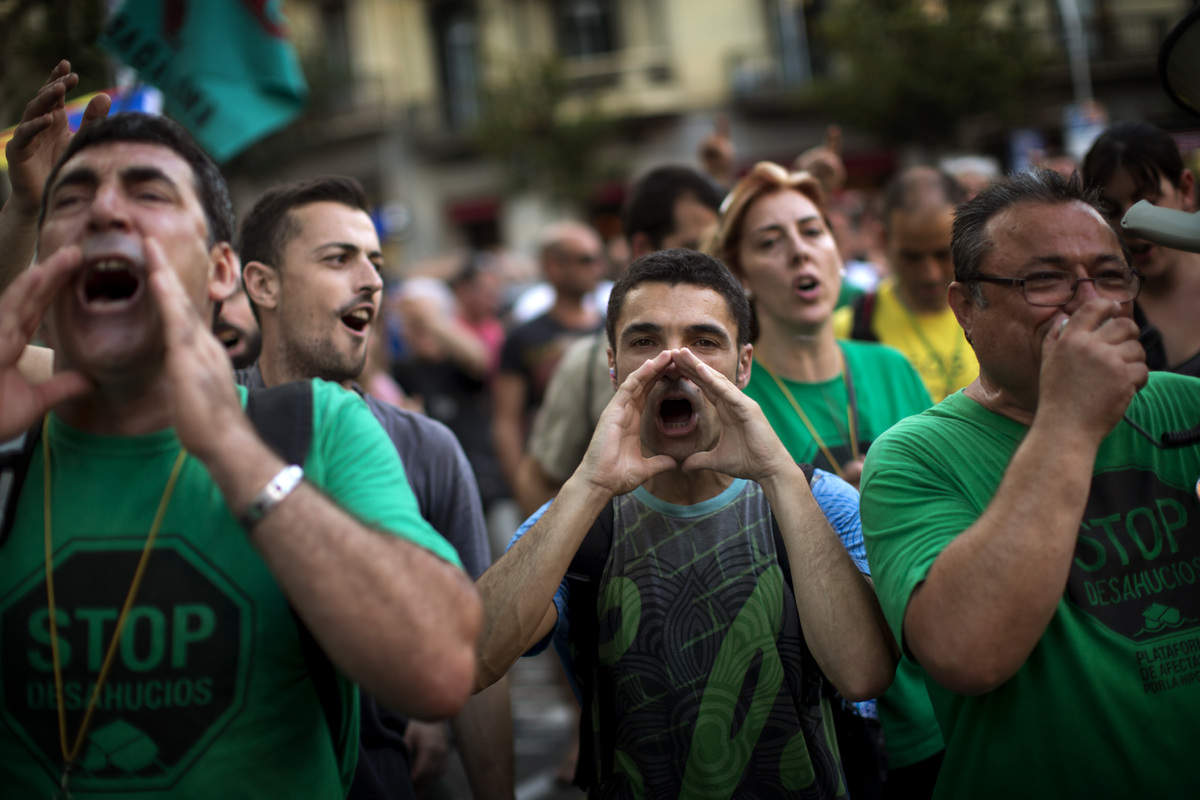 Demonstrators shout slogans against the government in front of the delegation of the Spanish government in Catalonia during a