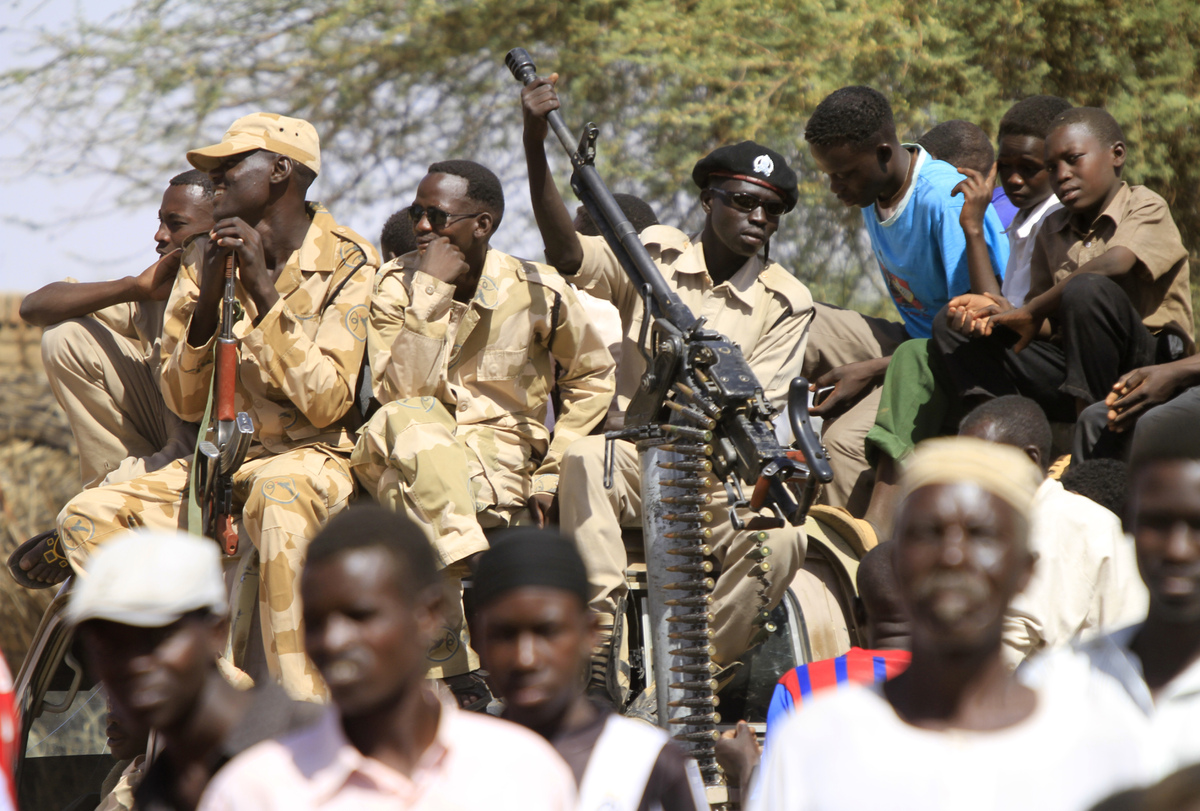 Sudanese soldiers keep watch as they sit next to civilians in the Shangil Tobaya area for displaced people in North Darfur st