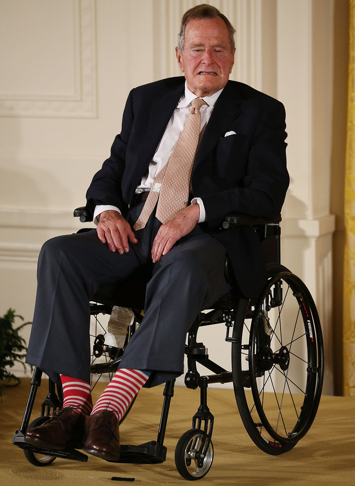Former President George H. W. Bush wears red stripped socks as he sits in a wheelchair during an event in the East Room at th