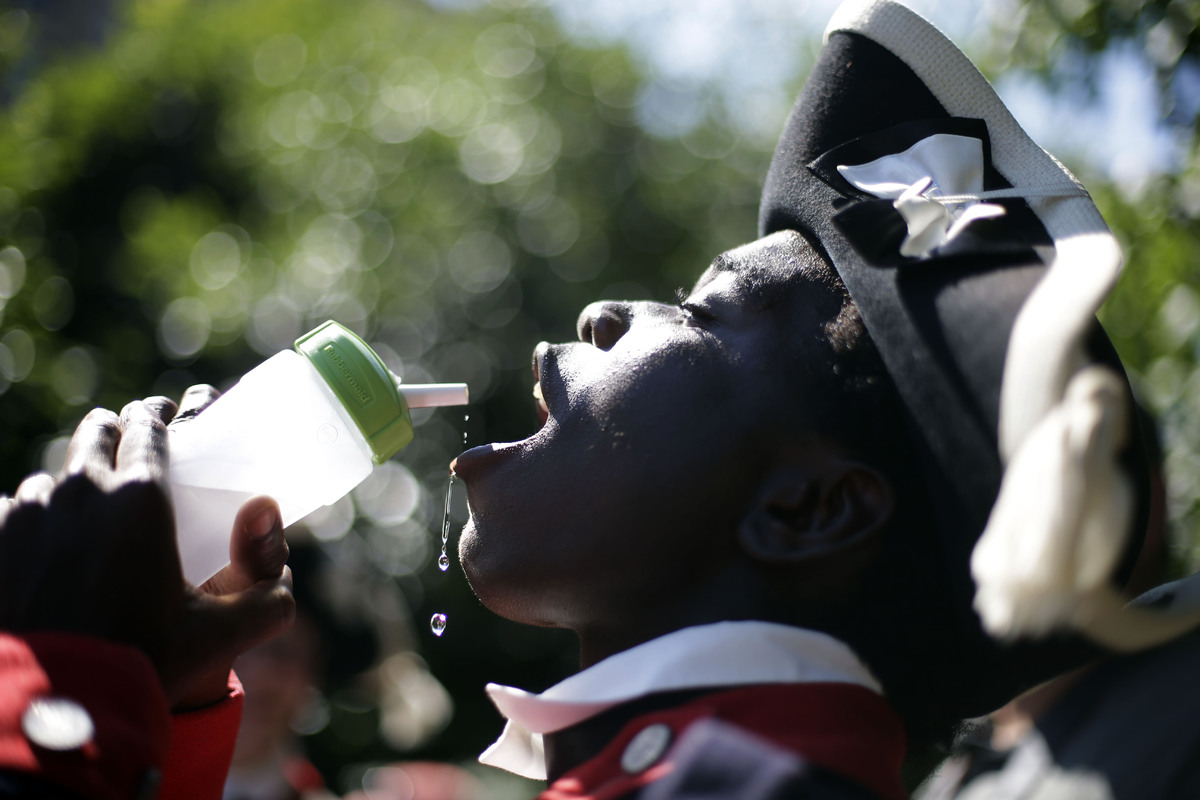 Dressed in a wool uniform Binyah Howard, 14, with the Plymouth Fife and Drum Corps takes a drink near Independence Hall, Tues