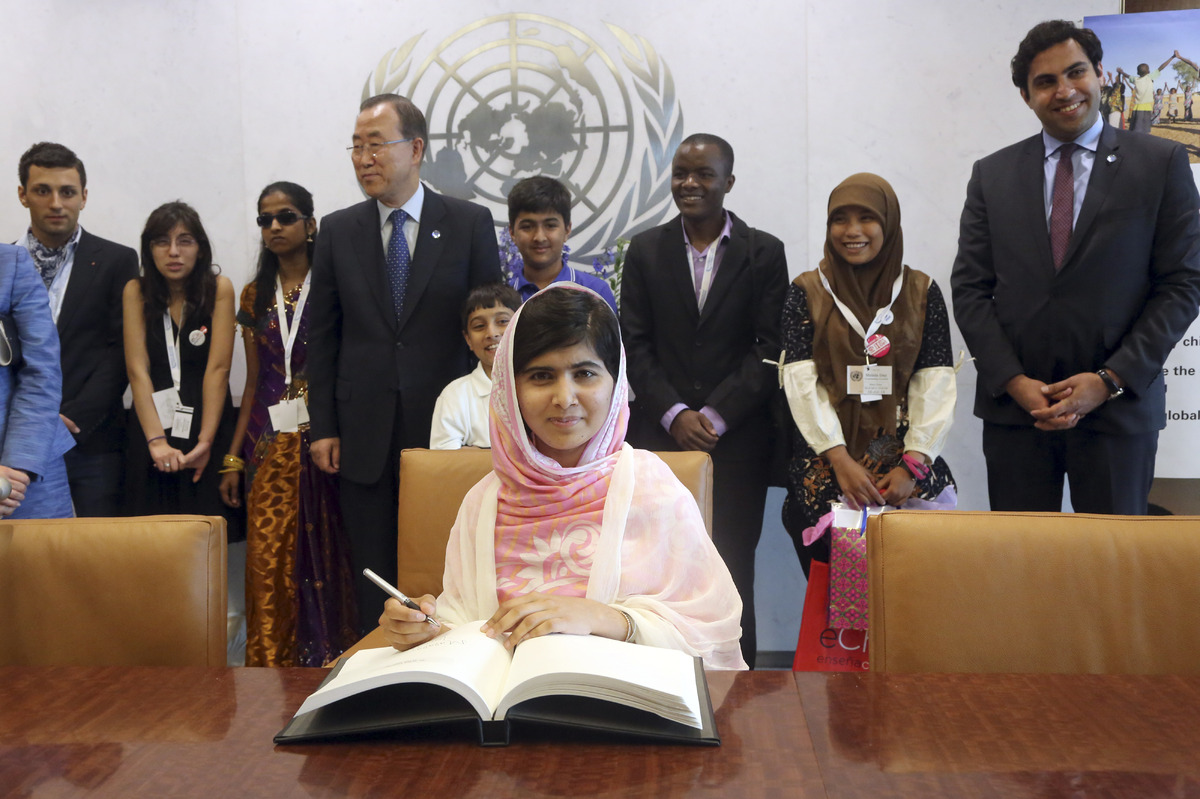 Malala Yousafzai signs United Nations Secretary-General Ban Ki-moon's guest books as Ban Ki-moon, center, and youth delegates