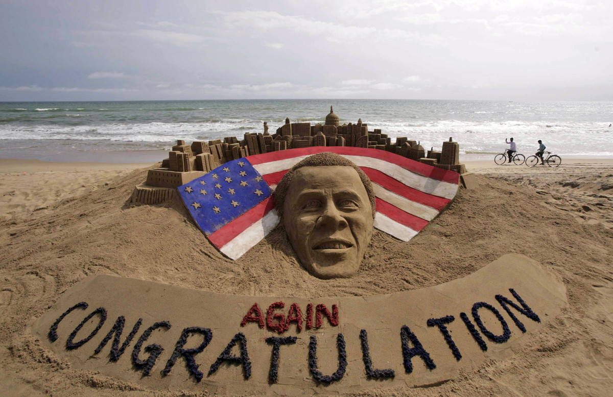 Cyclists ride on a beach passing by a sand sculpture congratulating U.S. president Barack Obama for a second term in office i