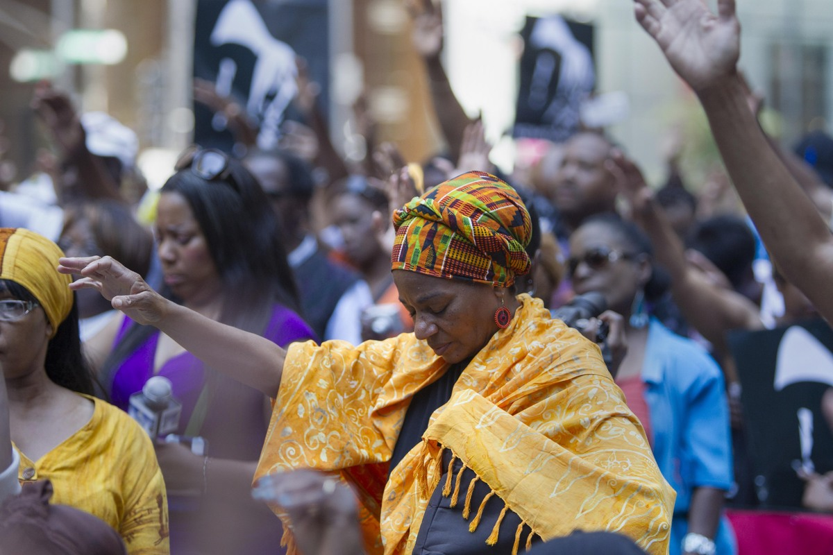 """Participants at the """"Justice for Trayvon"""" rally in Chicago raise their hands during a benediction, Saturday, July 20, 2013. T"""