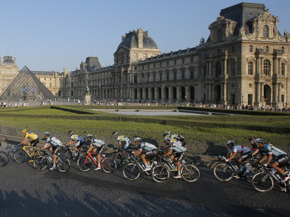 The pack, with Christopher Froome of Britain, wearing the overall leader's yellow jersey, left, rides through the courtyard o