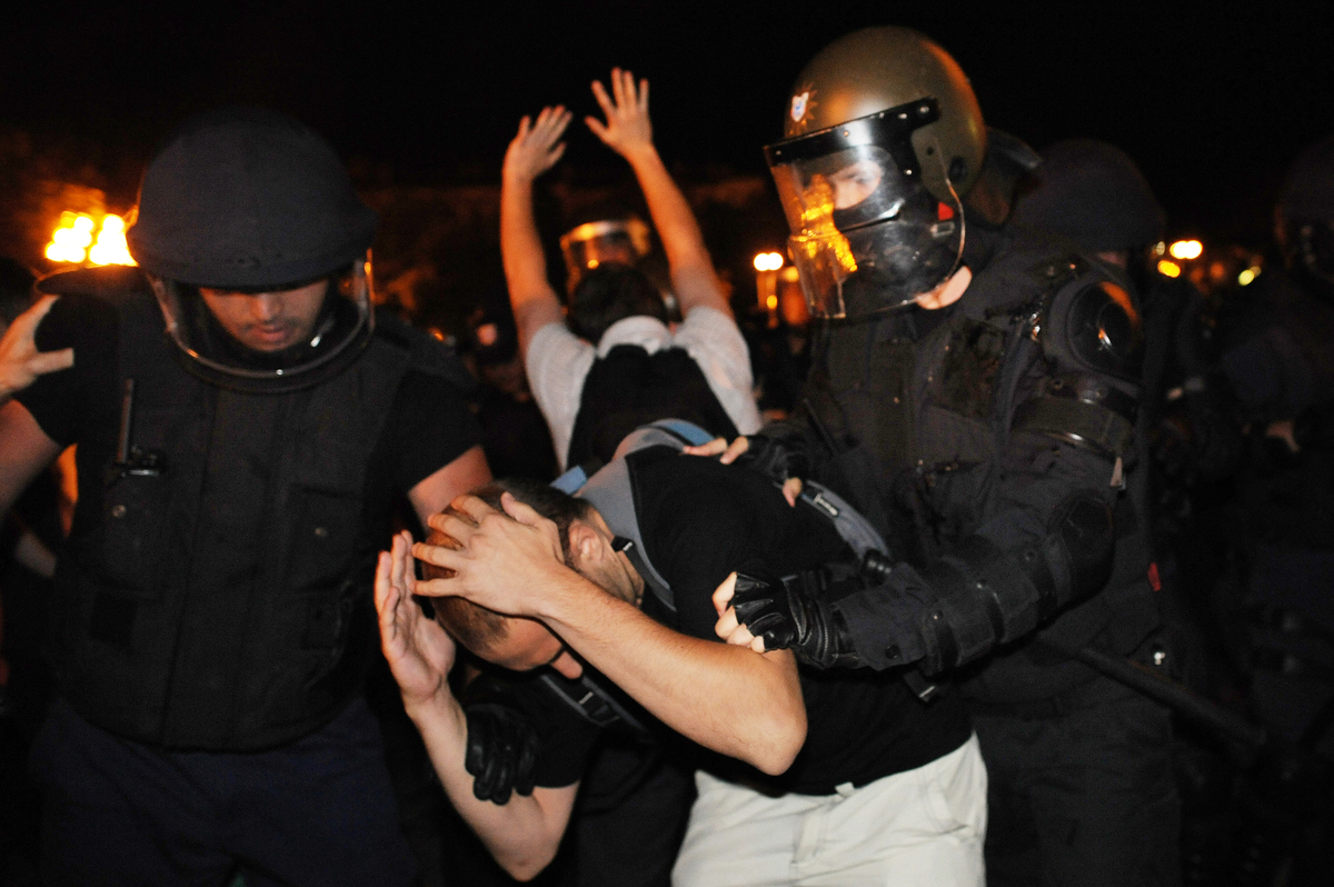 A protestor protects his head as he was pushed by riot policemen during an anti-government protest in Sofia on July 23, 2013.