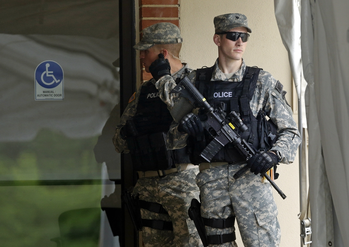 Military police stand guard outside of a courthouse in Fort Meade, Md., Monday, June 3, 2013, on the first day of Army Pfc. B