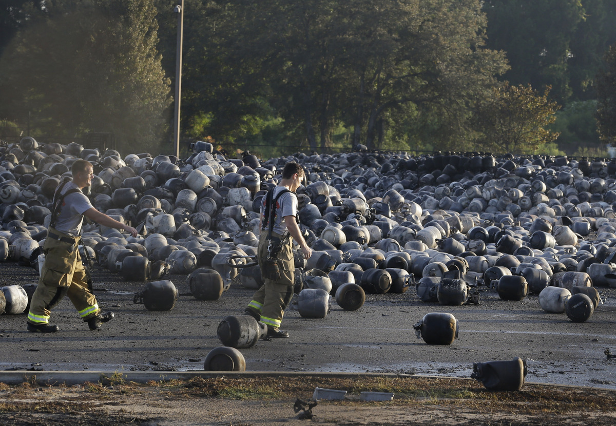 Firefighters walk through a sea of propane cylinders on the grounds of a propane gas company after a series of explosions roc