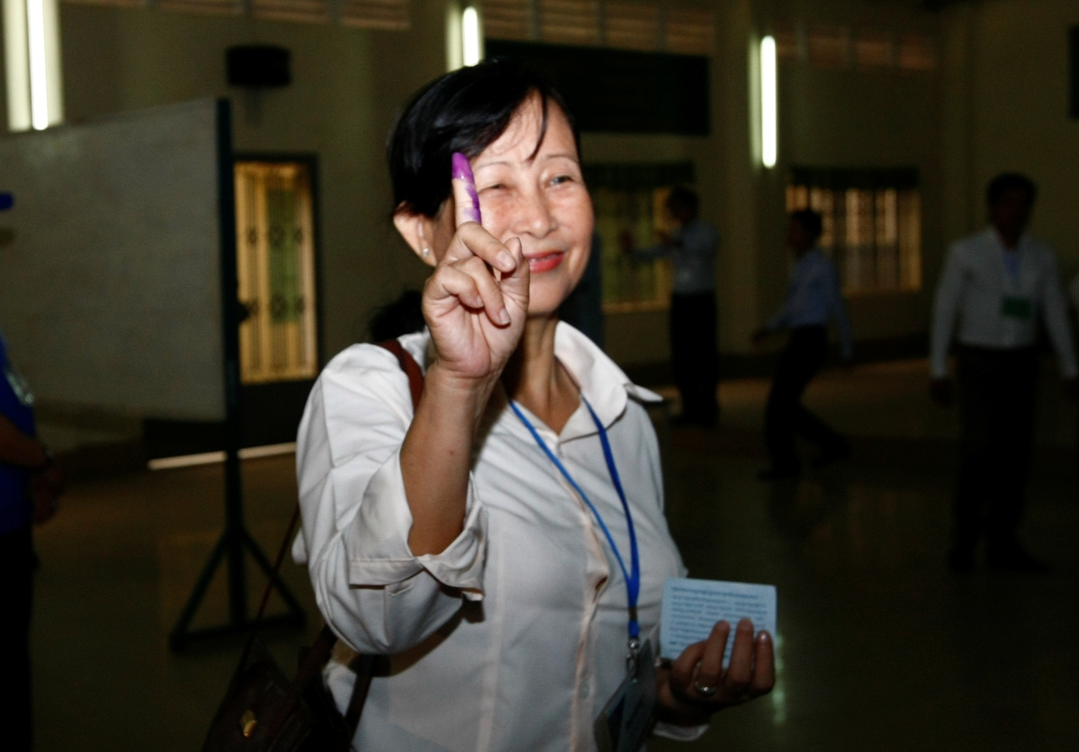 A villager shows off her inked finger at a polling station in Takhmau, south of Phnom Penh, Cambodia, Sunday, July 28, 2013.