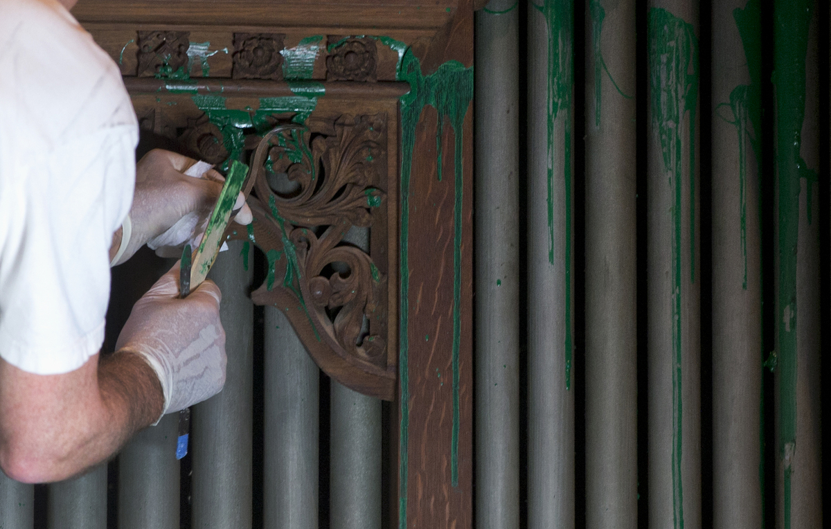 William Adair of Gold Leaf Studios removes green paint from the organ in the Washington National Cathedral's historic Bethleh