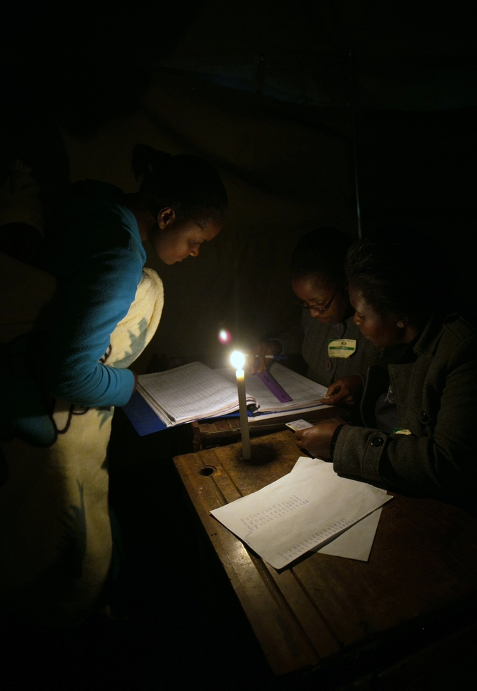 In this Wednesday, July 31, 2013 photo, voting takes place by candlelight in Harare. President Robert Mugabe's ZANU PF party