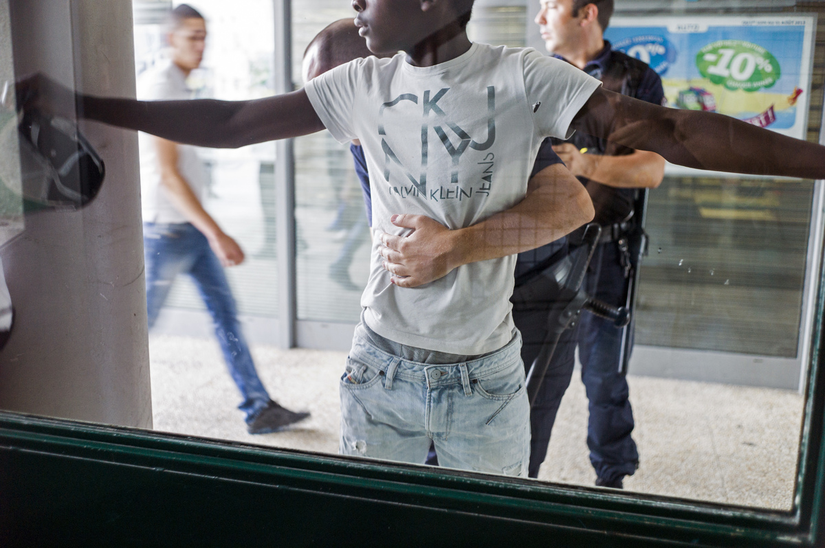 A policeman frisks a man in a priority security zone (ZSP) in Saint-Denis, a Paris suburb on July 30, 2013. (FRED DUFOUR/AFP/