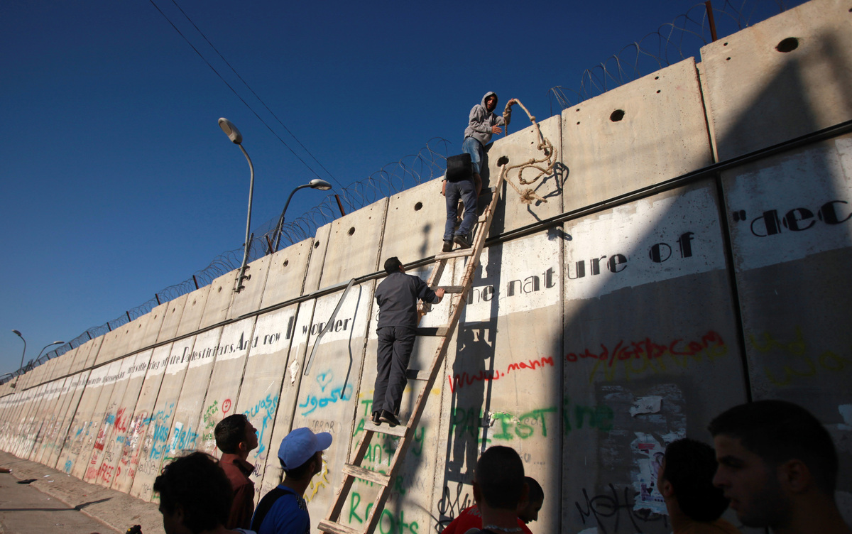 Palestinian men climb a section of Israel's separation barrier as they try to avoid crossing Israeli-controlled checkpoints t