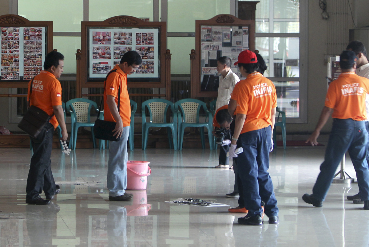 Police investigators inspect the site where a bomb is suspected to have been placed at at he Ekayana Grha Buddhist temple in