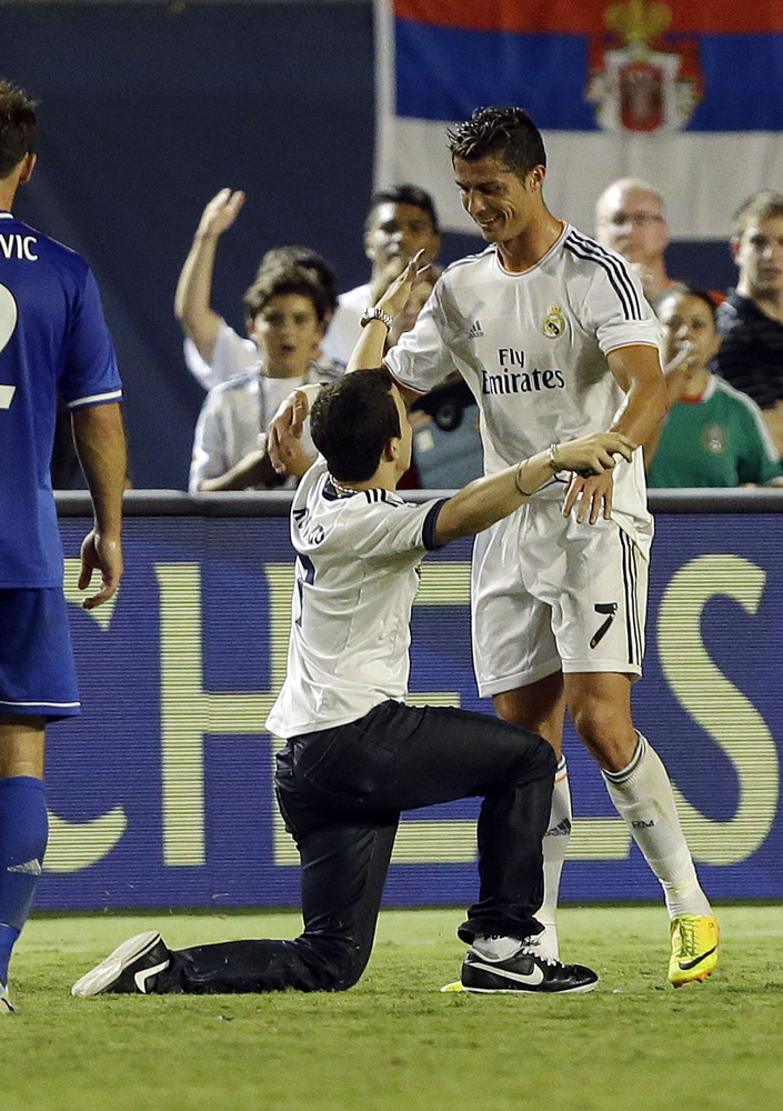 A man gets on the field and kneels before Real Madrid forward Cristiano Ronaldo (7) during the second half of Real Madrid's I