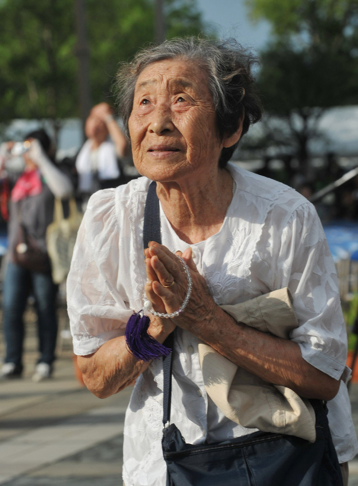 An elderly woman prays in front of the Peace Statue at the Peace Memorial Park in Nagasaki, western Japan on August 9, 2013 a
