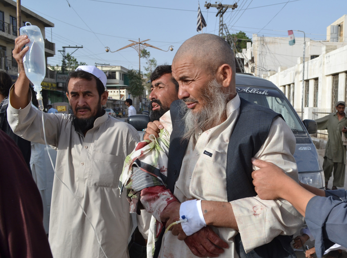 People rush an injured man to a hospital in Quetta, Pakistan on Friday, Aug. 9, 2013. (AP Photo/Arshad Butt)