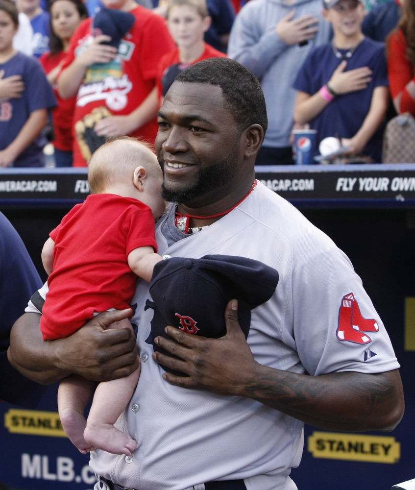 Boston Red Sox' David Ortiz holds a fan's baby during the national anthem before their baseball game against the Kansas City