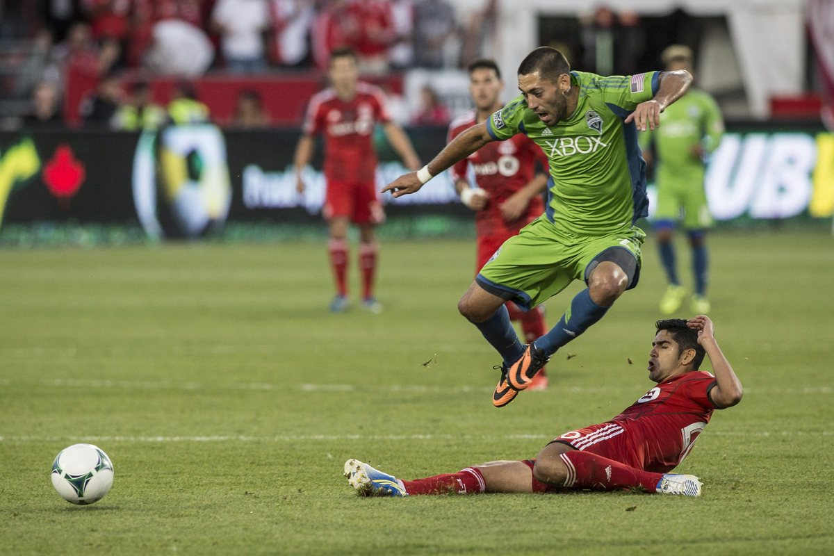 Seattle Sounders' Clint Dempsey, left, is tackled by Toronto FC 's Matias Laba during the second half of their MLS soccer gam