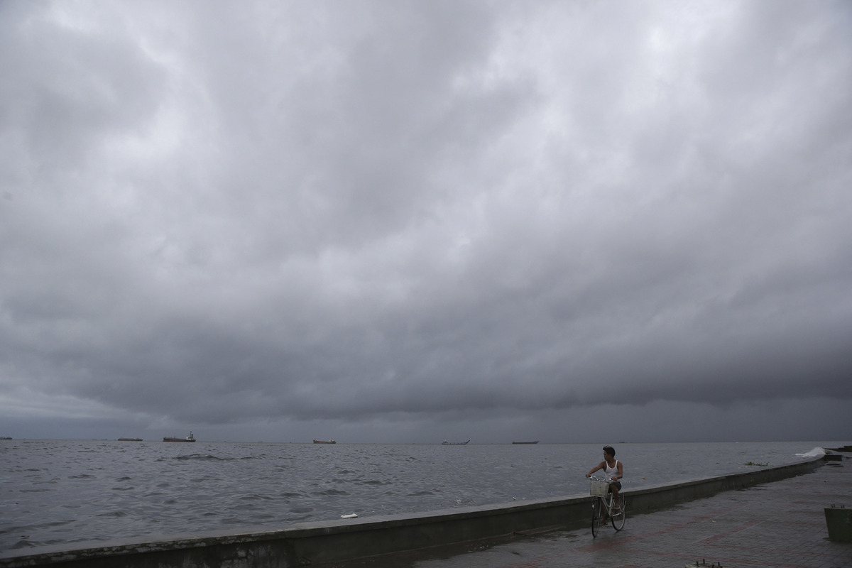 A Filipino man ride his bicycle as thick clouds form in Navotas, north of Manila, Philippines on Monday, Aug. 12, 2013. (AP P