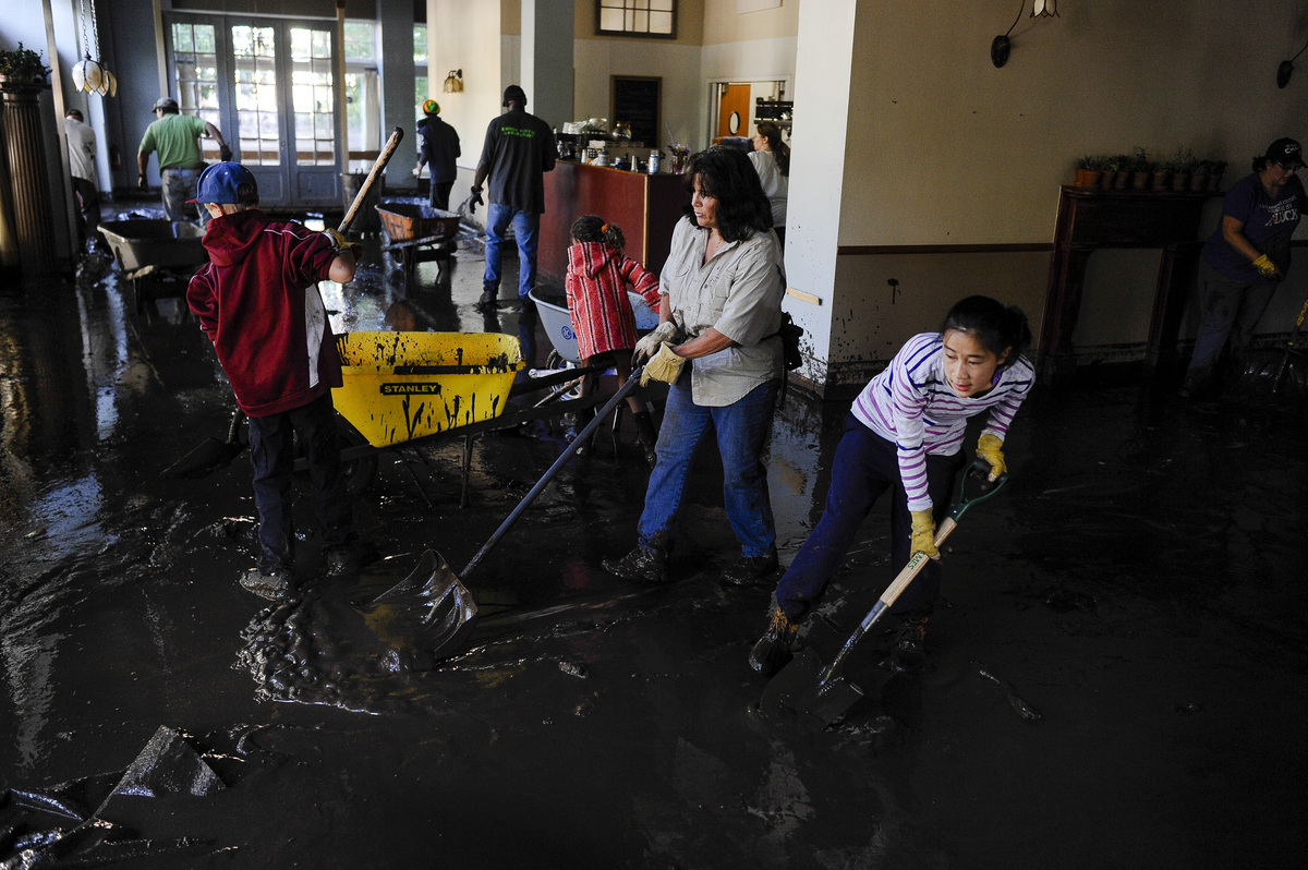 Abby Kingman, 14, helps shovel a four-inch coat of mud out of Adam's Mountain Cafe Saturday, Aug. 10, 2013 in Manitou Springs