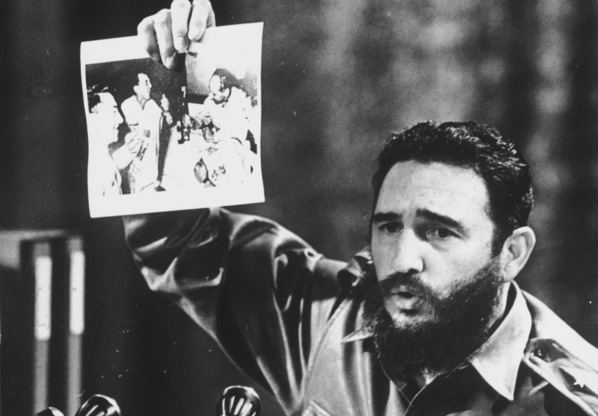 5th July 1968: Cuban Prime Minister Fidel Castro, presents a photograph in which General Ovando Candia and other men of the B