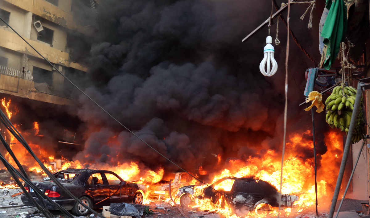 Flames rise from the site of a car bomb between the Bir el-Abed and Roueiss neighbourhoods, in the southern suburb of Beirut