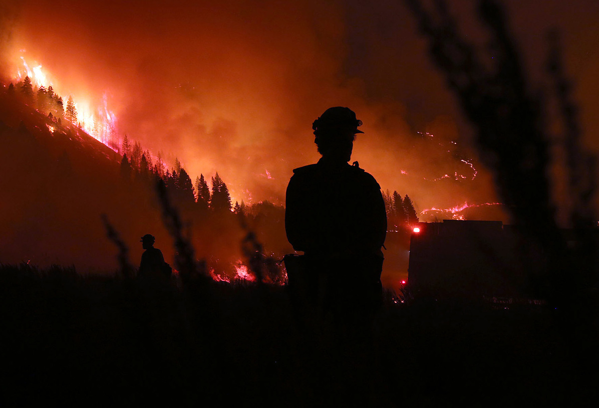 In this Aug. 14, 2013, photo, members of the Idaho City Hotshots work on burnout operations around Pine, Idaho, where the Elk