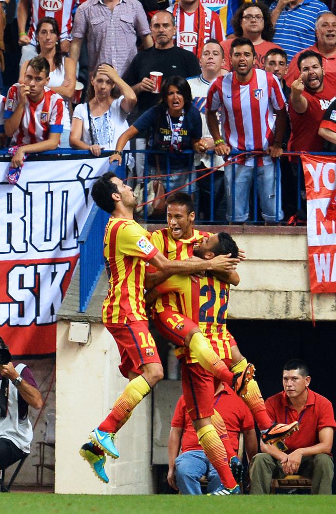 Barcelona's midfielder Sergio Busquets (L) and Barcelona's Brazilian defender Dani Alves (R) congratulate Barcelona's Brazili