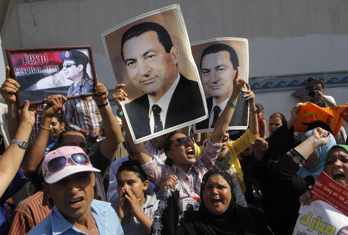 Supporters of Egypt's former Egyptian President Hosni Mubarak hold his posters and a poster of Egyptian Army Chief Lt. Gen. A