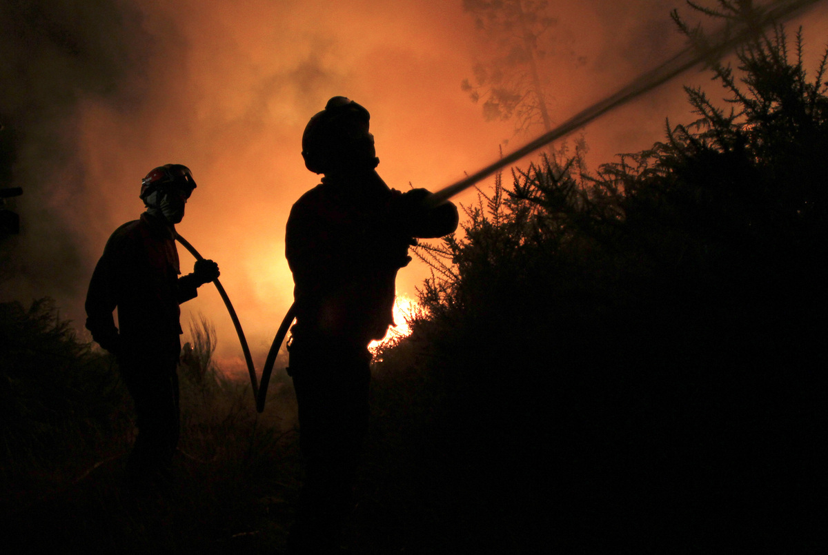 Portuguese firefighters work on a fire in Tondela, near Viseu, Portugal, Thursday night, Aug. 22, 2013. (AP Photo/Francisco S