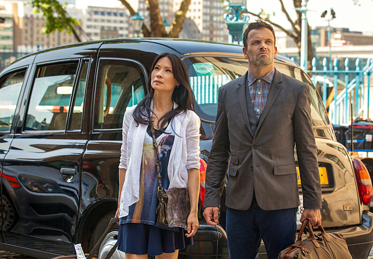 Holmes (Jonny Lee Miller, right) and Watson (Lucy Liu, left) travel to London to help track down an old mentor and find thems
