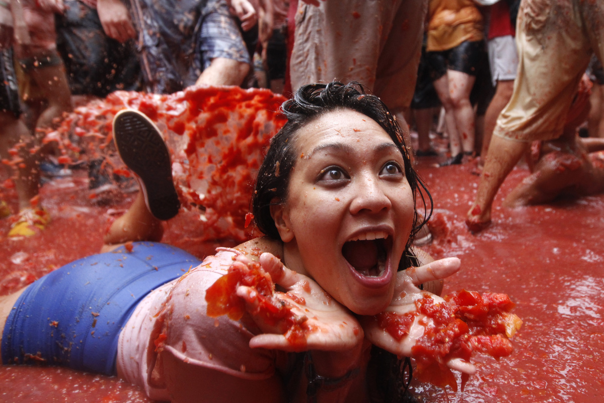 """A woman lies on a puddle of tomato juice during the annual """"tomatina"""" tomato fight fiesta in the village of Bunol, 50 kilomet"""