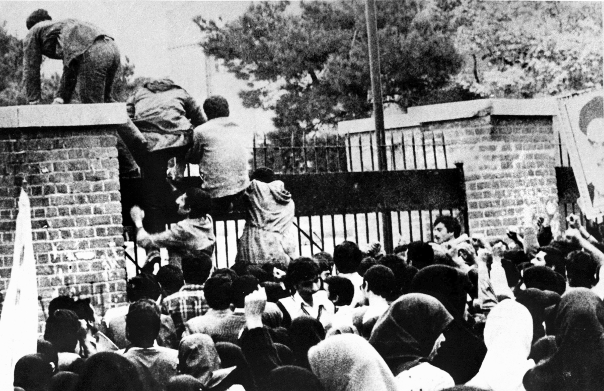 Iranian students climb over the wall of the U.S. embassy in Tehran during the Iranian Revolution, 4th November 1979. (Photo b