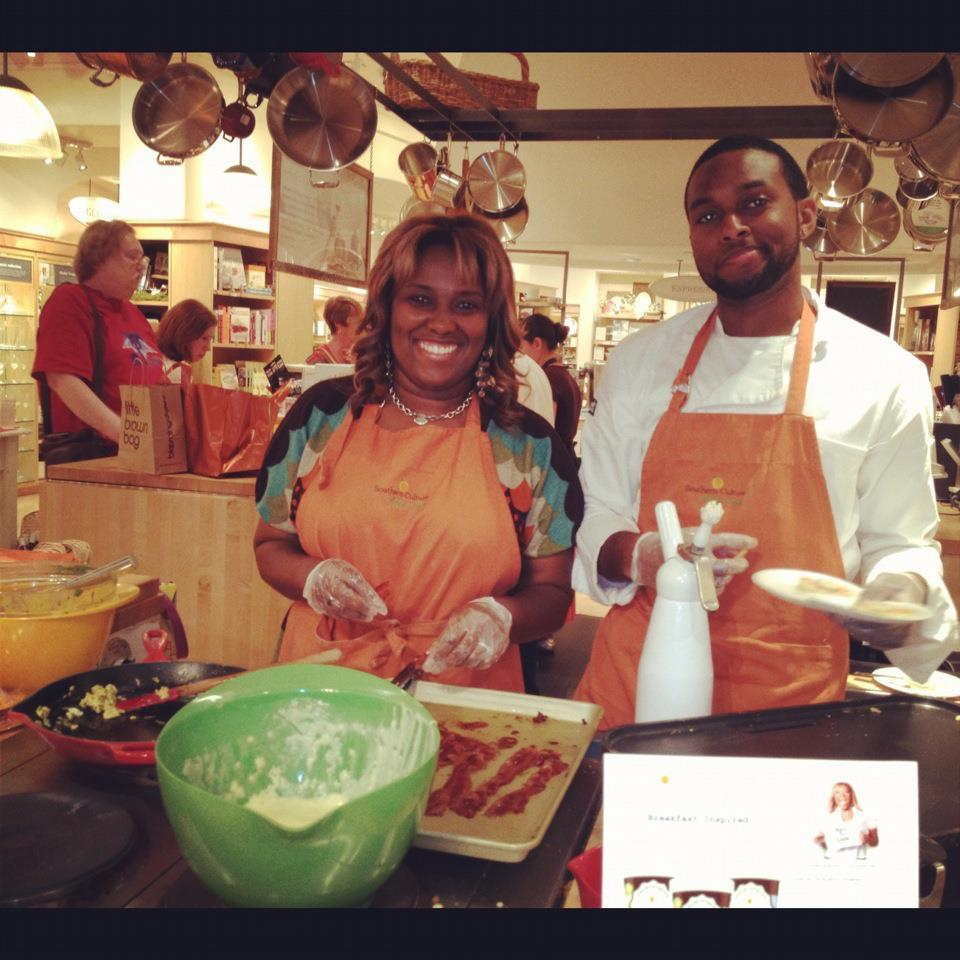 Erica and employee Michael Lloyd cook for shoppers at Williams Sonoma. This is where Erica came up with the Candied Bacon con