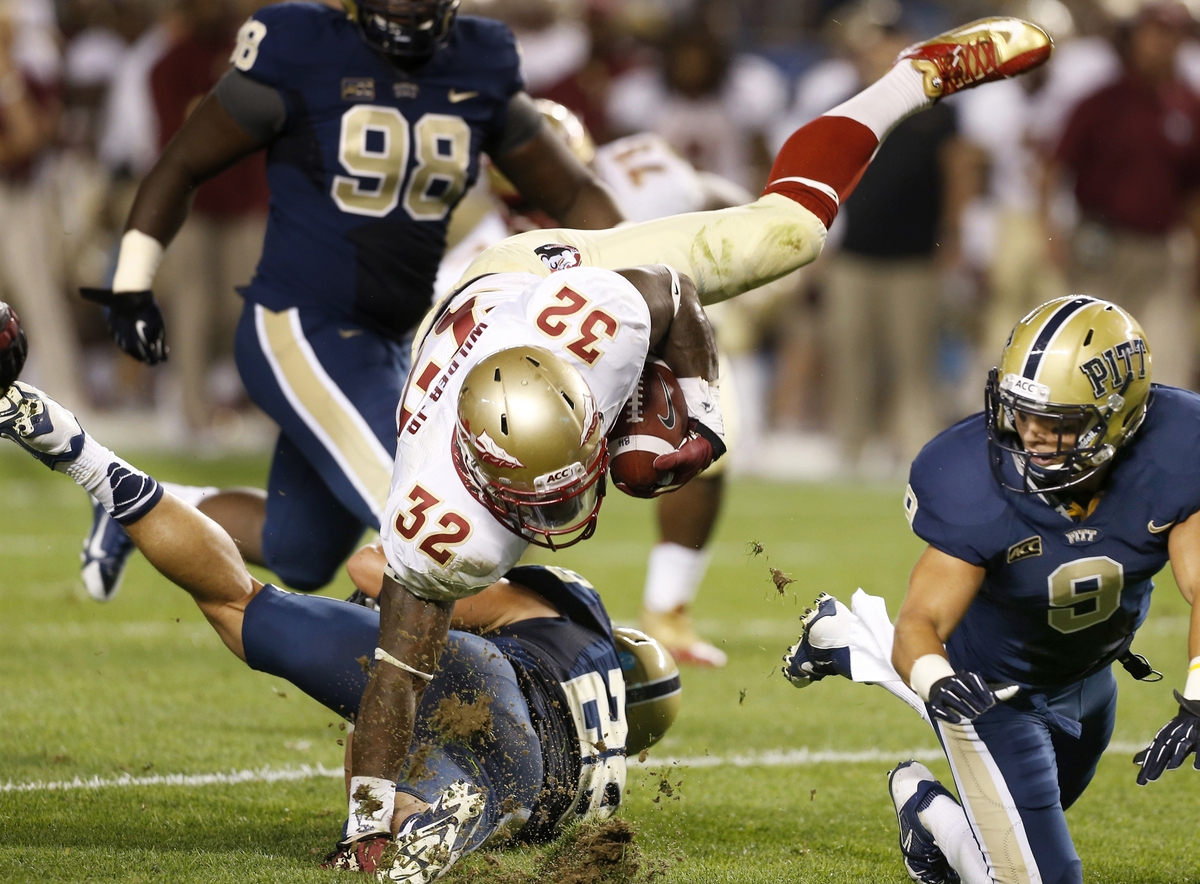 Florida State running back James Wilder (32) tumbles over Pittsburgh linebacker Anthony Gonzalez (28) as linebacker Todd Thom