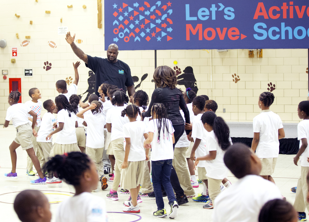 First lady Michelle Obama and NBA basketball great Shaquille O'Neal join exercises with pupils at Orr Elementary in Washingto
