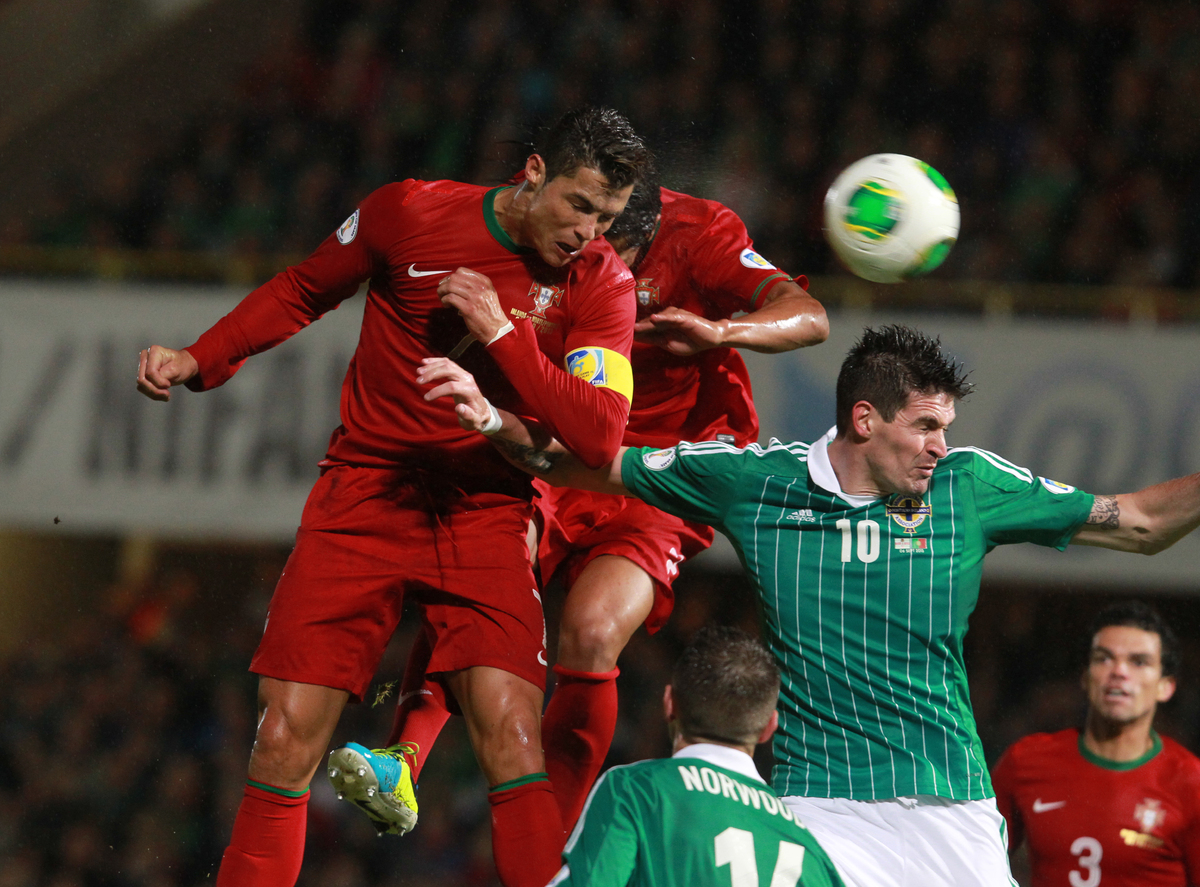 Portugal's Cristiano Ronaldo, left, scores a goal despite the intentions of Northern Ireland's Kyle Lafferty, right, during t
