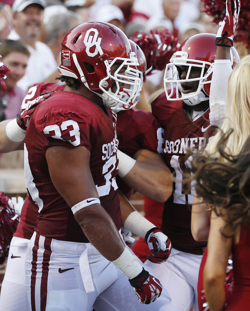 Oklahoma fullback Trey Millard (33) is congratulated by his teammates following a touchdown against West Virginia in the seco