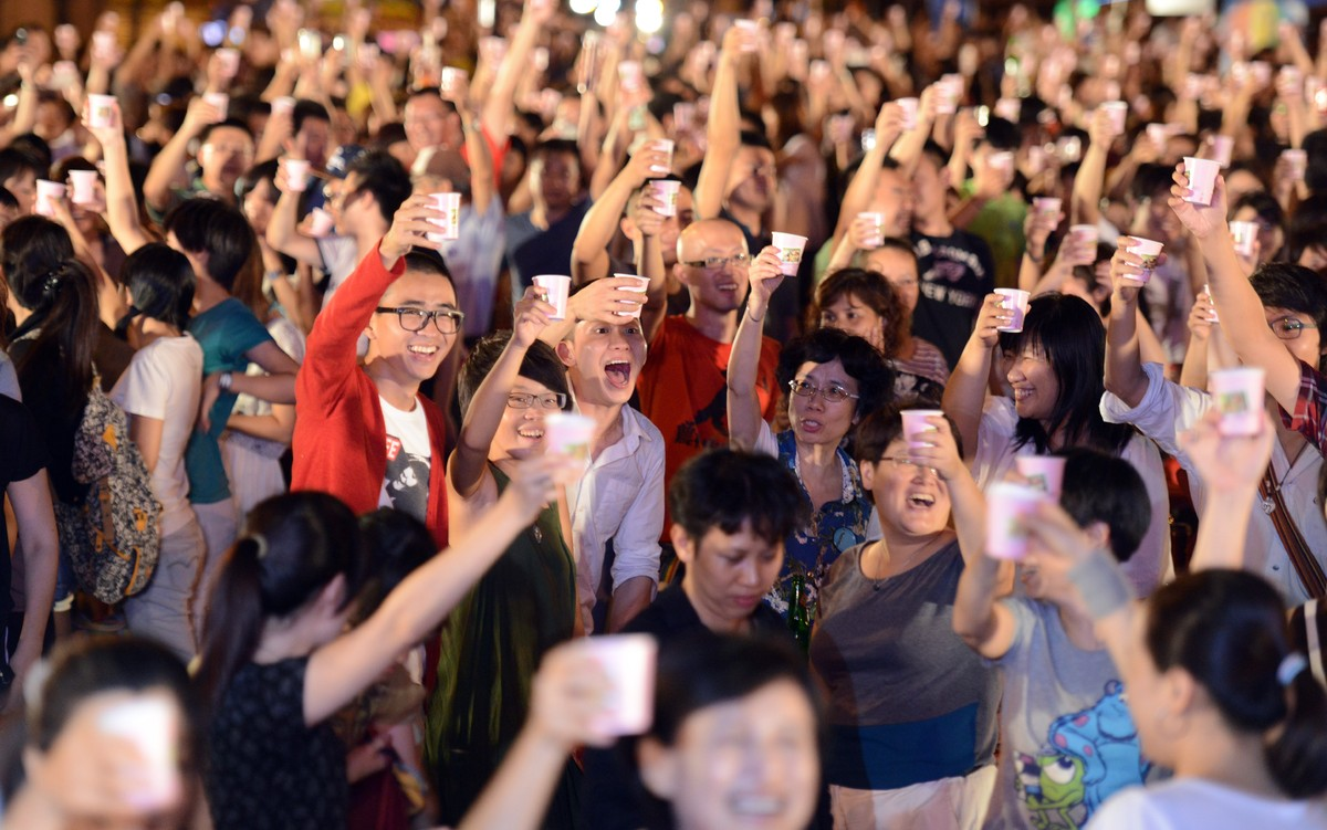 Local residents toast each others during a same sex dinner party in front of the Presidential Office in Taipei on September 7