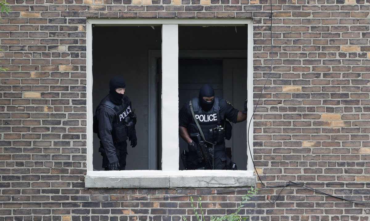 Authorities search an abandoned building for a man who escaped a courthouse in Detroit, Monday, Sept. 9, 2013. Derreck White,