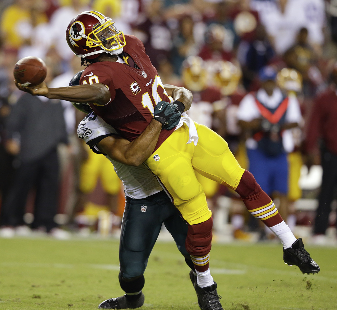 Washington Redskins quarterback Robert Griffin III (10) tries to get off a pass as he wrapped up by Philadelphia Eagles outsi