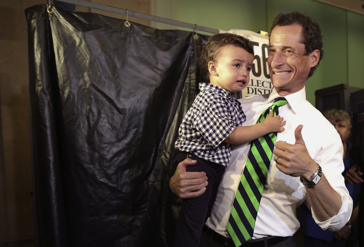 Democratic mayoral hopeful Anthony Weiner holds his son Jordan as he leaves the voting booth after casting his vote at his po