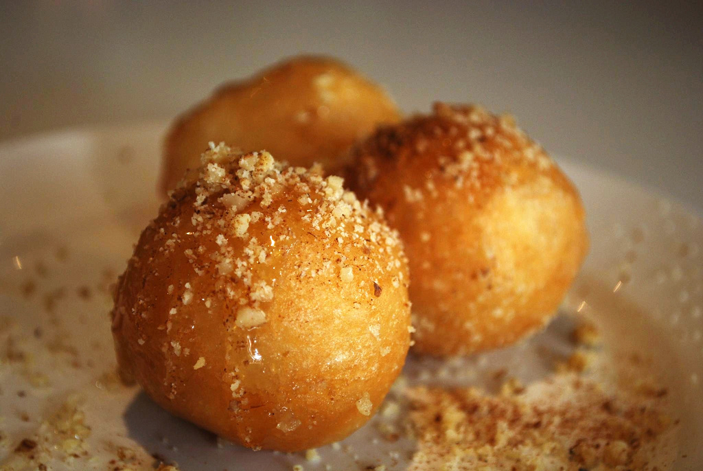 This Greek delicacy consists of fried dough topped with honey and cinnamon.