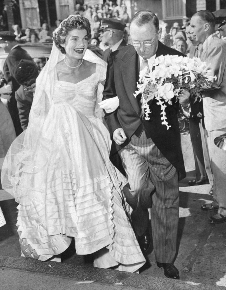 A smiling Jacqueline Bouvier arrives at St. Mary's Church in Newport, R.I., on the arm of her stepfather, Hugh D. Auchincloss