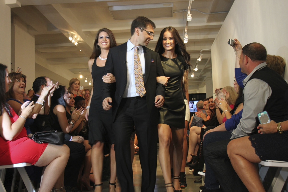 New Jersey plastic surgeon Ramtin Kassir is flanked by two patients at Faces of Fashion, a surgery-themed runway show timed t