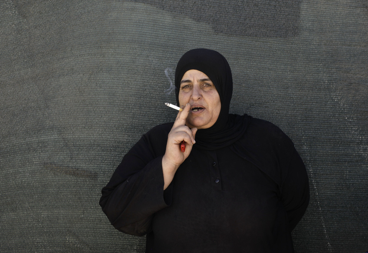In this Wednesday, Sept. 11, 2013 photo, a Syrian woman smokes a cigarette outside her tent at a temporary refugee camp in th