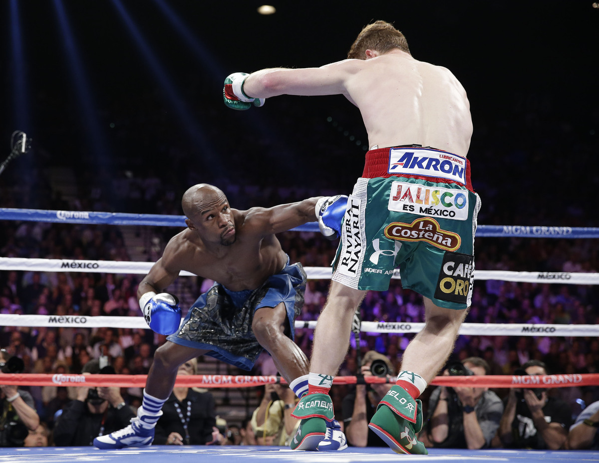 Floyd Mayweather Jr. throws a low jab against Canelo Alvarez in the first round during a 152-pound title fight, Saturday, Sep