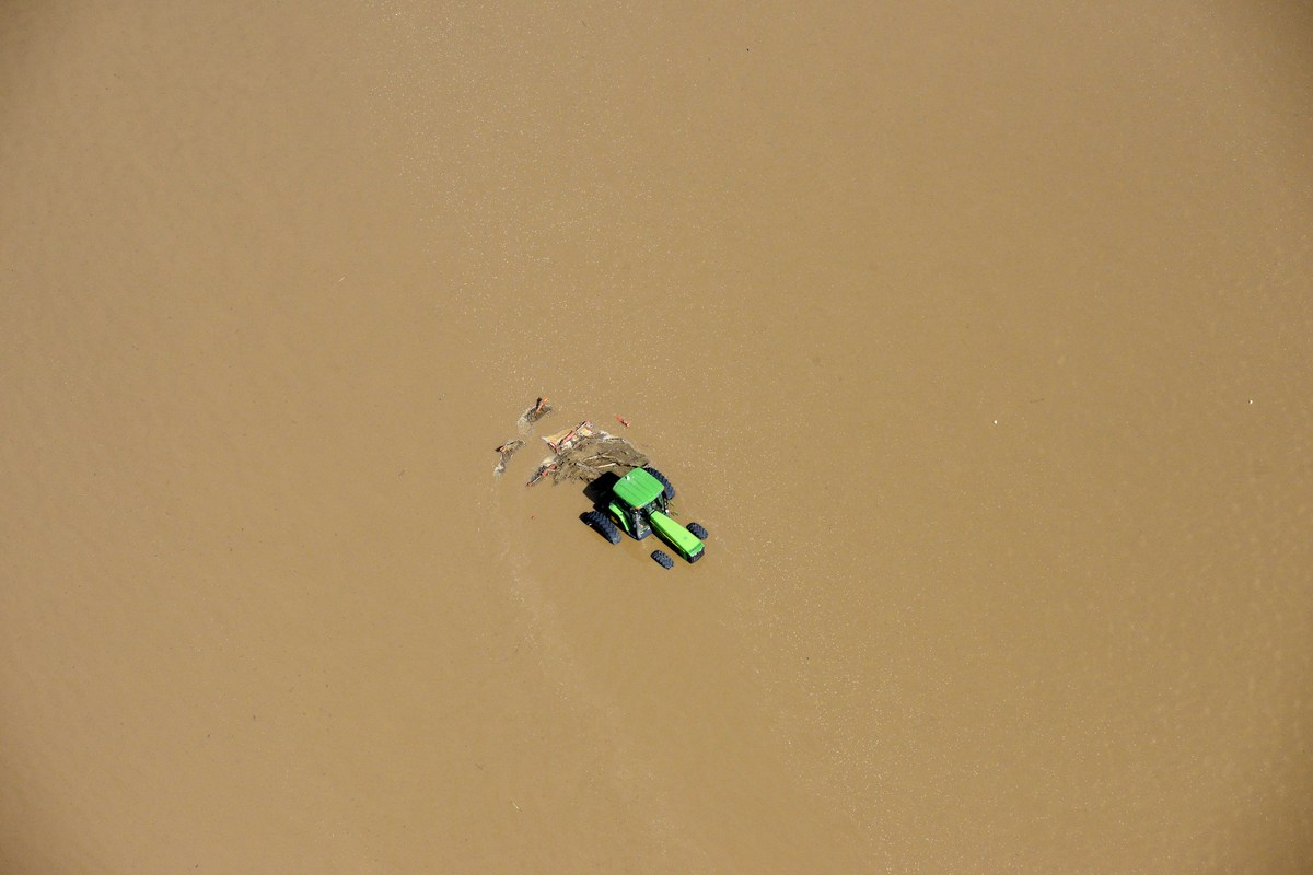 A tractors sits partially submerged in a farm field after flooding along the South Platte River in Weld County, Colorado near